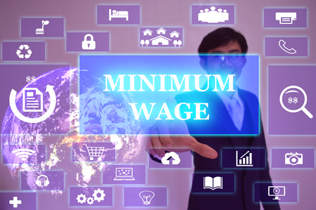minimum wage: MINIMUM WAGE concept  presented by  businessman touching on  virtual  screen