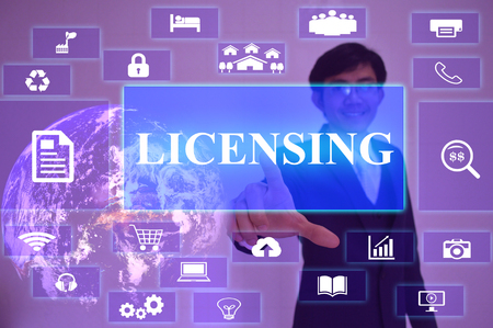 licensing: LICENSING concept  presented by  businessman touching on  virtual  screen Stock Photo