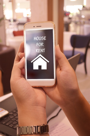 well maintained: business and modern lifestyle concept  young woman using house for rent  app online in the coffee shop Stock Photo