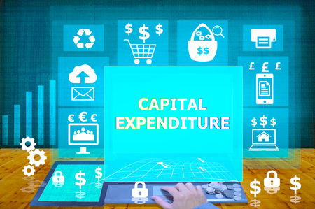 expenditure: technology and biz concept. working on his laptop in the secured office, select  icon capital expenditure on the virtual display