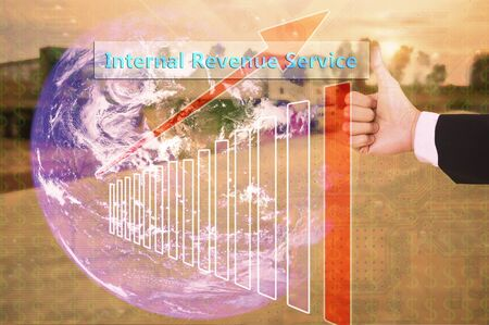 internal revenue service: touching Internal Revenue Service on virtual screen vintage tone , image element furnished by NASA