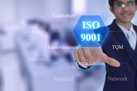 ISO 9001 concept touched by a businessman on virtual screen Stock Photo
