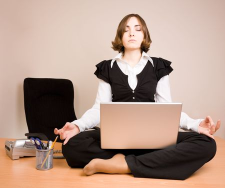 Young woman sitting in lotus pose on the desk photo