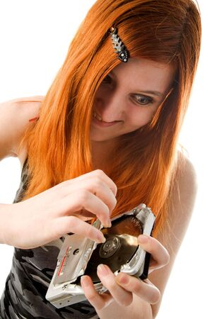 Red haired girl tearing old hard drive (focus on girl) Stock Photo - 6360887