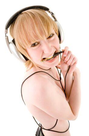 Blond girl in headphones holding plug in teeth Stock Photo - 6366526