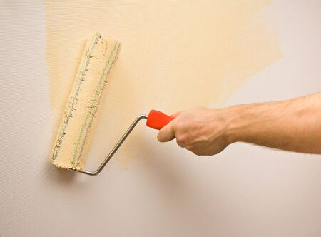 Picture of a hand painting the wall with roller photo