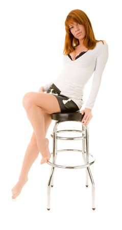 Red haired girl sitting on a bar chair photo