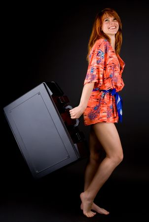 Red haired girl with huge suitcase photo