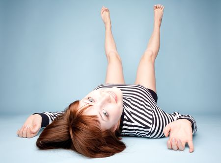 Smiling girl lying upside down on blue background photo