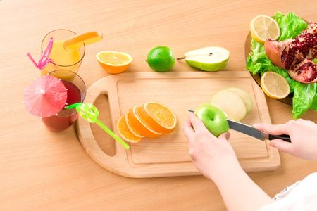 Womans hands with knife cutting apple photo