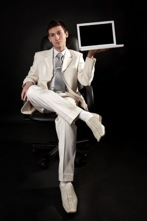 Young man in white costume with laptop Stock Photo - 6400492