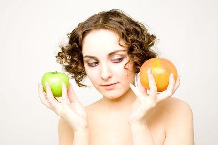 Beautiful curly girl chooses between an apple or grapefruit photo