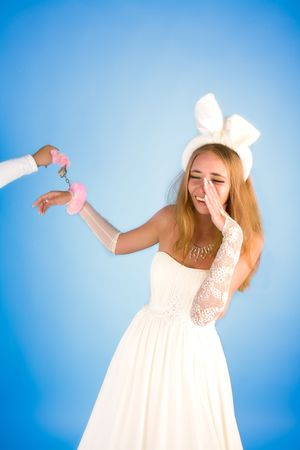 Beautiful girl in wedding dress and rabbits ears smiling photo