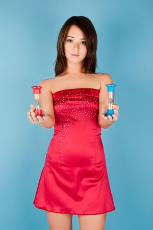 Beautiful girl in red dress with sand-glass photo