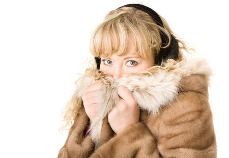 Beautiful blond girl in fur coat and headphones photo