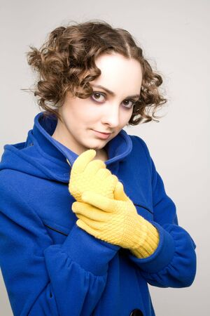 Beautiful woman in yellow gloves and blue coat photo