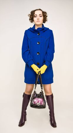 Beautiful woman in yellow gloves and blue coat with handbag standing photo