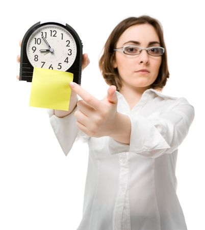 expires: Beautiful girl points to clock with sticky (focus on clock) Stock Photo