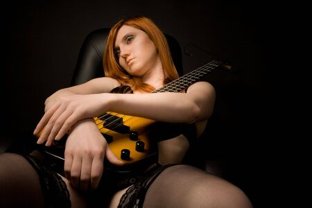 Beautiful rocked woman with guitar sitting on the chair photo