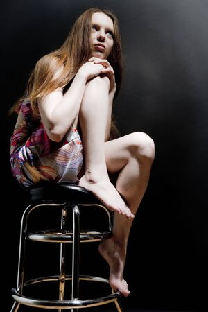 Young woman sitting on the bar chair and dreaming photo