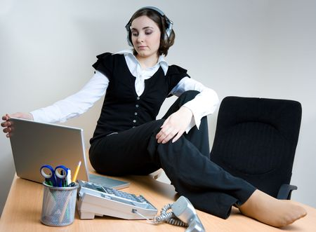 Young woman sitting on the desk and listening to music in headphones photo