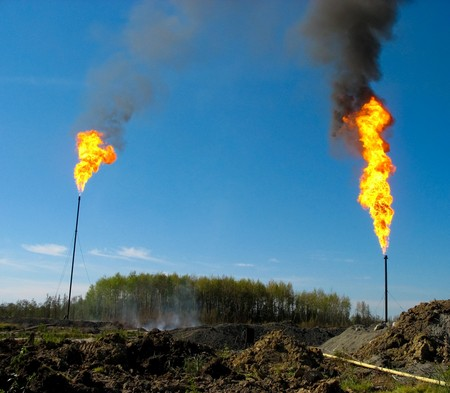 Two large and smoking oil flares photo