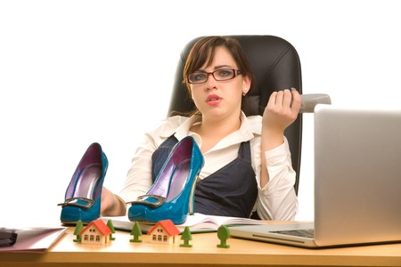 Businesswoman with telephone in her hands and shoes on the desk photo
