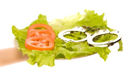 Healthy food and handcuffs on the plate Stock Photo - 7011900