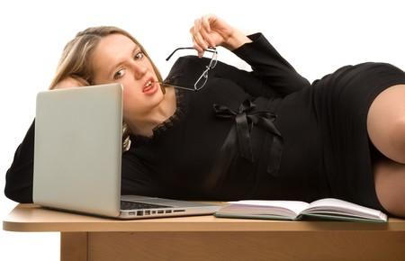 Sexy businesswoman lying on the desk and holding the rim of an eye-glass in her mouth photo