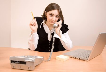 appointee: Young secretary with  telephone, laptop and pencil calling by phone Stock Photo