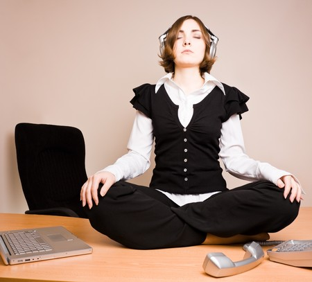 Young woman sitting in lotus pose and listening to music in headphones photo