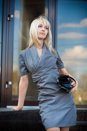 Young woman in grey dress outdoors photo
