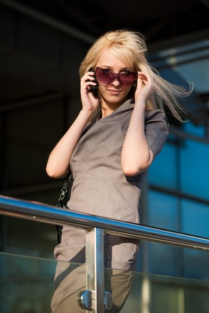 Girl holding sunglasses calling to phone photo