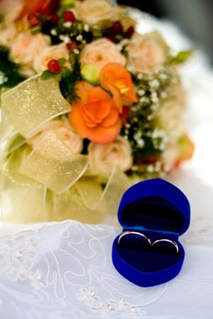 Two gold wedding rings in blue box and bunch of flowers photo