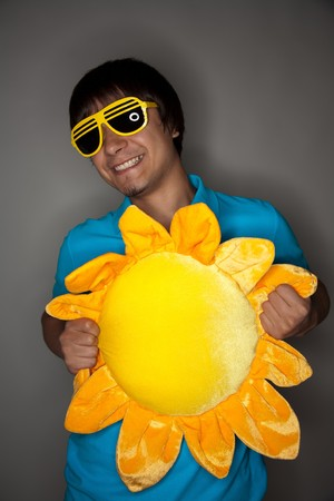 Young showman in glasses smiling and holding toy sun photo