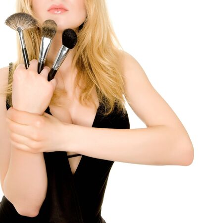 young blond woman holding make-up brushes photo