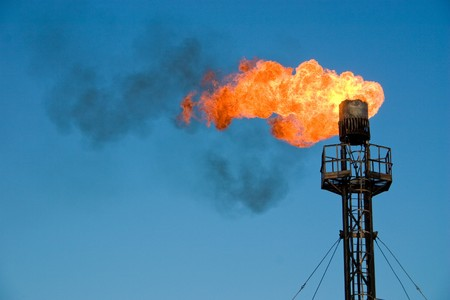 mining: Burning oil flare on a blue sky Stock Photo