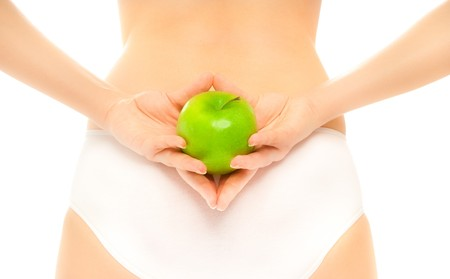 Womans back  in white panties holding an apple photo