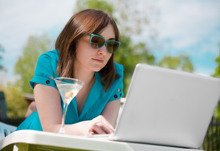 Businesswoman with laptop and glass of martini outdoors photo
