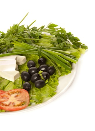 A plate of lettuce, feta, onion, black olives and tomatoes photo