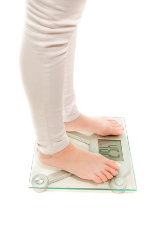 Womans legs with weighing scales photo