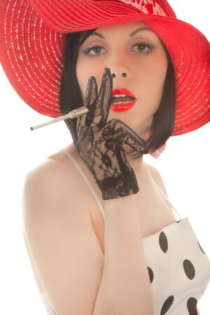 Retro-styled woman with cigaret in her hand looking to the camera isolated on white photo