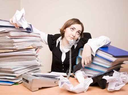 Giovane donna in carriera con tonnellate di documenti chiamare telefono