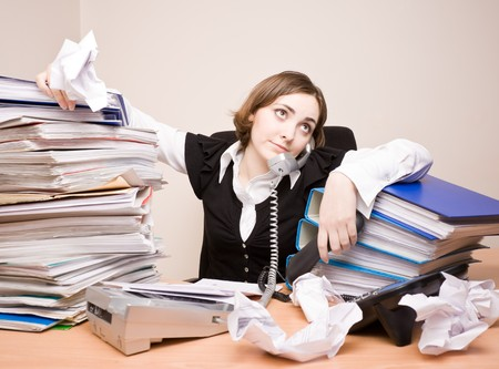 Young businesswoman with tons of documents calling phone photo