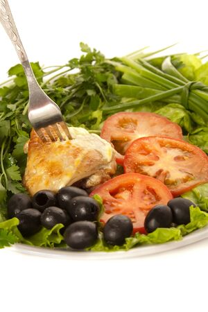 A plate of burning chicken, tomatoes, olives and lettuce with fork photo