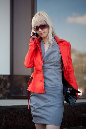 Beautiful woman in red jacket  calling by phone outdoors photo