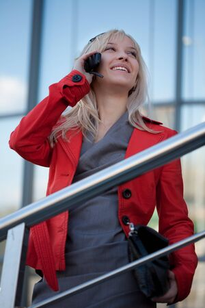 Woman calling by phone and smiling outdoors photo