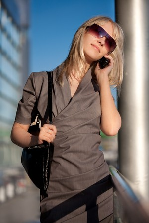 Beautiful woman in sunglasses with cellphone walking photo