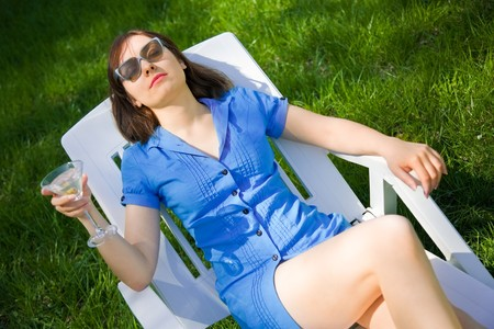 Woman lying on the sun lounger with a glass of martini photo