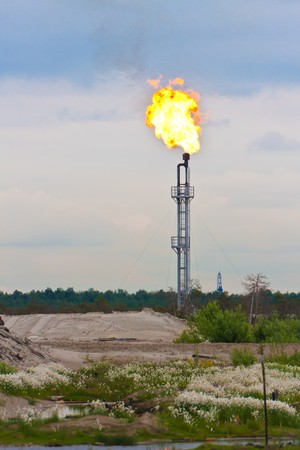 gas burner: Burning oil flare on cloudy sky